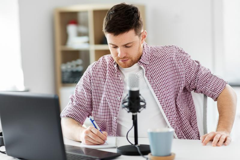 Audio blogger with laptop, microphone and notebook stock photography