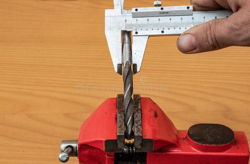 The technology of measuring the diameter of the drill, using calipers stock photos