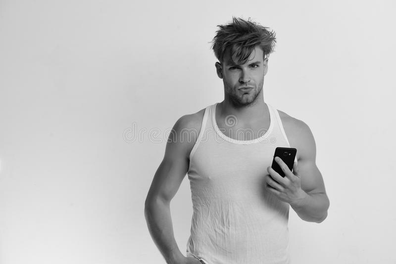 Technology and modern lifestyle concept. Man holds gadget in hand. Guy with confident face. Isolated light grey background, copy space. Man with mobile phone royalty free stock image
