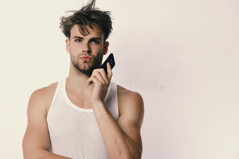 Technology and modern lifestyle concept. Man holds gadget. In hands and talks on it. Guy with interested face isolated on light grey background, copy space. Man royalty free stock photography