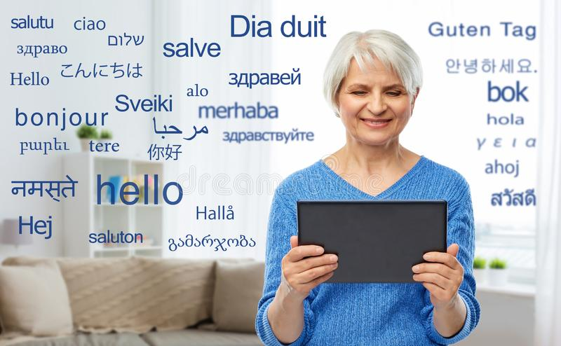 Senior woman using translator on tablet computer. Technology, online translator and old people concept - smiling senior woman using tablet computer over greeting stock photo