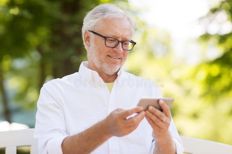Senior man with smartphone at summer park royalty free stock photography