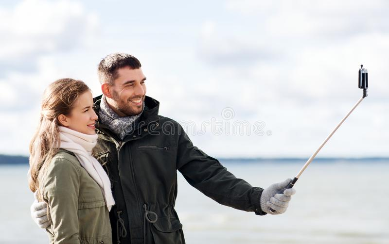Happy couple taking selfie on beach in autumn. Technology and people concept - smiling couple taking picture by smartphone on selfie stick on beach in autumn royalty free stock photo
