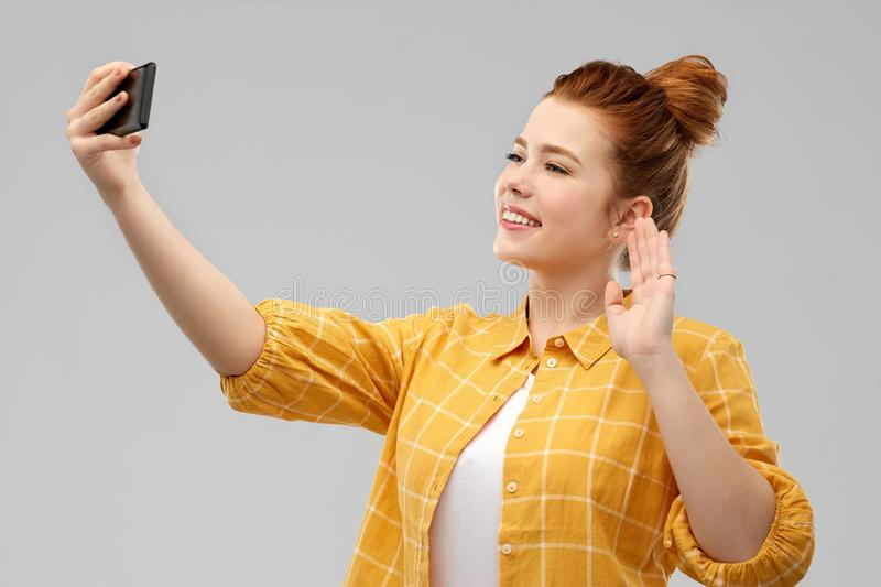Redhead teenage girl taking selfie by smartphone stock photography