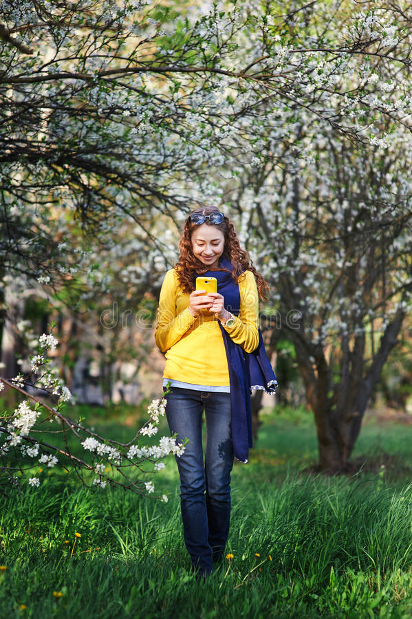 Technology and people concept - smiling young woman texting on smartphone stock photos