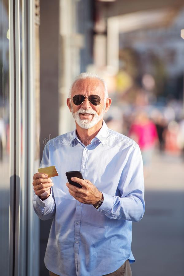 Technology, people, lifestyle and communication concept - senior man texting message on smartphone in city stock image