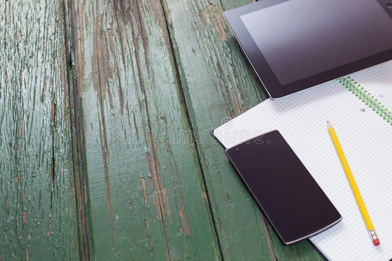 Technology products, phone and tablet on green wood with pencil and notebook royalty free stock images