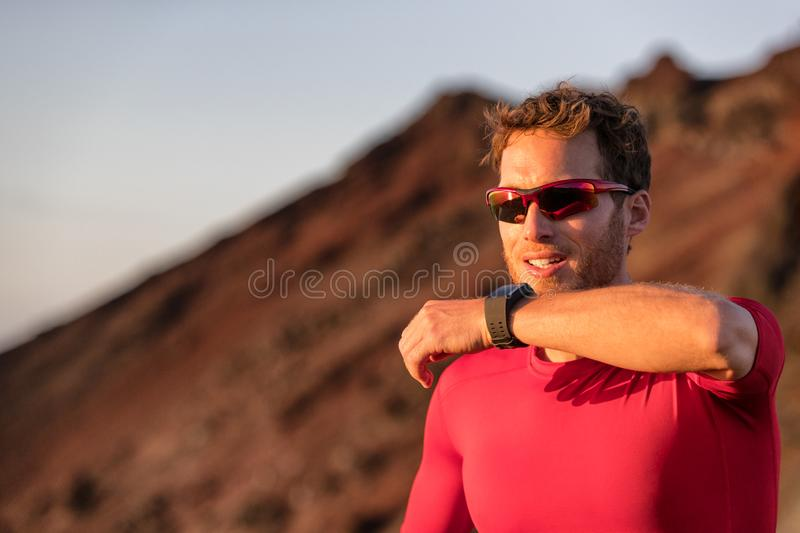 Technology for sport and active living. Athlete man talking into smartwatch wearable tech device speaking to someone or dictating. Message on smart watch app royalty free stock image