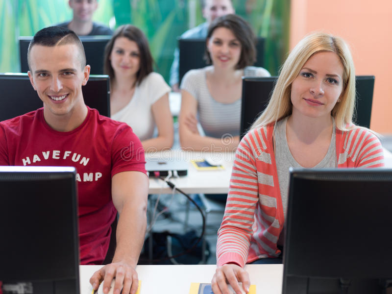 Technology students group in computer lab school classroom. Working on stock image