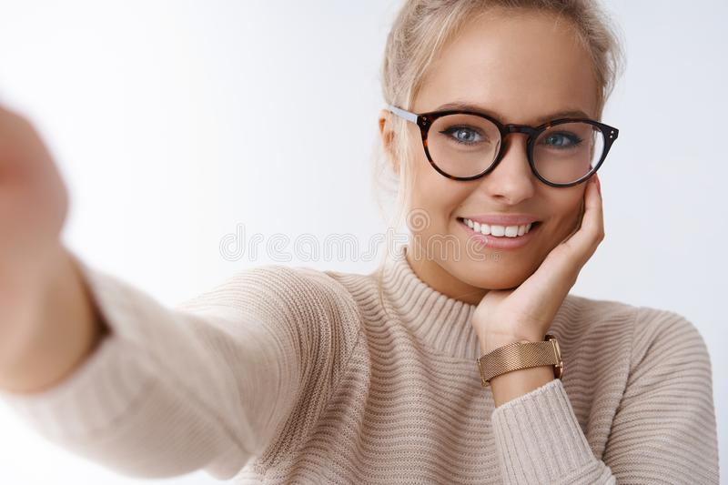 Technology, tenderness and beauty concept. Tender good-looking girlfriend taking selfie holding camera extend hand royalty free stock photos