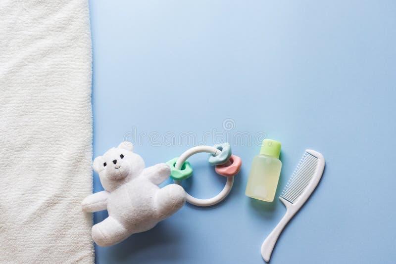 Tecido dos bens dos bebês, brinquedo do bebê, champô, óleo no fundo azul com espaço da cópia Vista superior ou configuração lisa imagens de stock royalty free