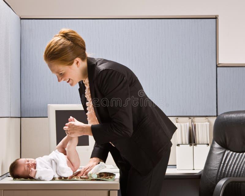 Tecido em mudança do bebê da mulher de negócios na mesa imagem de stock