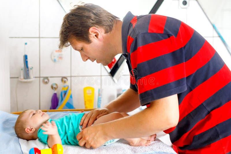Tecido em mudança do pai loving de sua filha bonito saudável do bebê Criança pequena, menina na tabela em mudança no banheiro com imagem de stock