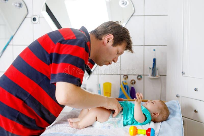 Tecido em mudança do pai loving de sua filha recém-nascida do bebê Criança pequena, menina na tabela em mudança no banheiro com c imagem de stock