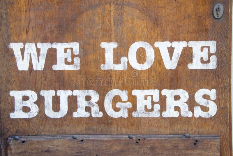 Tecken` älskar vi hamburgare` på träväggen royaltyfri fotografi