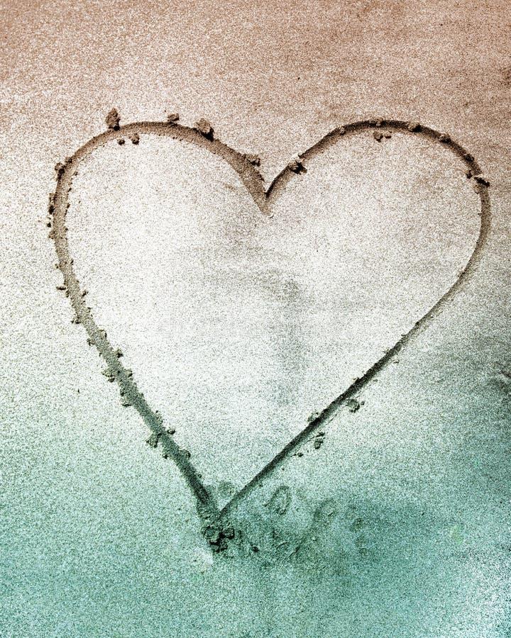 Tecken av förälskelsehjärta Shape på sand arkivfoton
