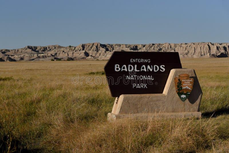 Tecken för Badlandsnationalparkingång med Badlands i bakgrund arkivbild