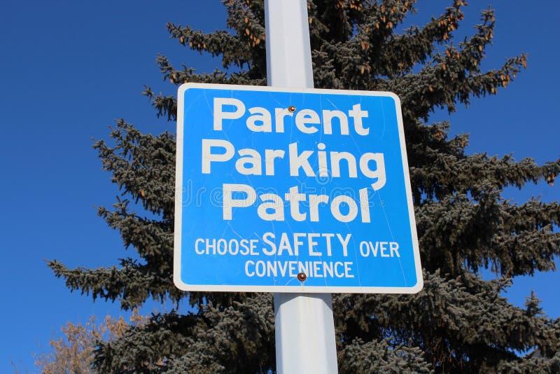 Tecken för förälderparkeringspatrull mot träd och blå himmel royaltyfria foton