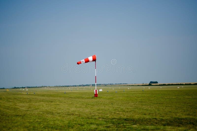 Tecken för flygfältvindriktning på det gröna gräset med lodisar för blå himmel royaltyfri foto