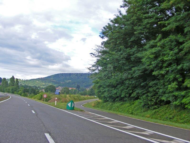 Tecken för gaffelföreningspunkt med tvärgator som spliting i tvåvägs Vägar sikt från bilen arkivfoto