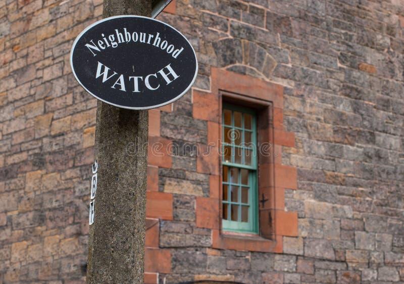 Tecken för grannskapklocka med fönstret på bakgrunden arkivbilder