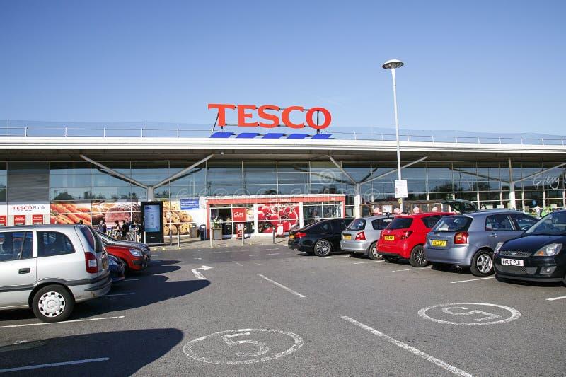 Tecken för huvudsaklig ingång och reklamfilmför ett lokalt Tesco lager med bakgrund för blå himmel arkivfoton