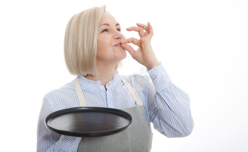Tecken för kockkvinnavisning för läckert Kvinnlig kock i likformig med det perfekta tecknet som rymmer den tomma plattan Tillfred royaltyfri fotografi