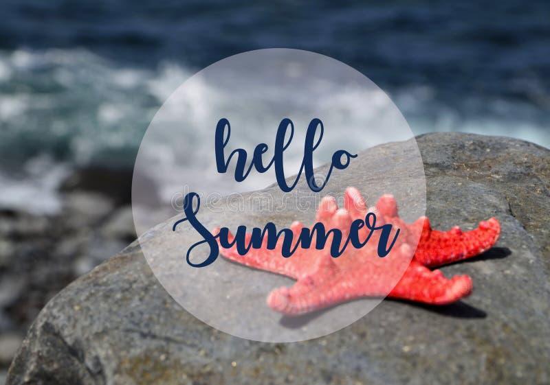 Tecken för meddelande för Hello sommarsemester med sjöstjärnan på stranden vid havet arkivbild