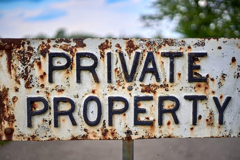 Tecken för privat egenskap för tappning Metalliskt och rostigt close upp arkivbild