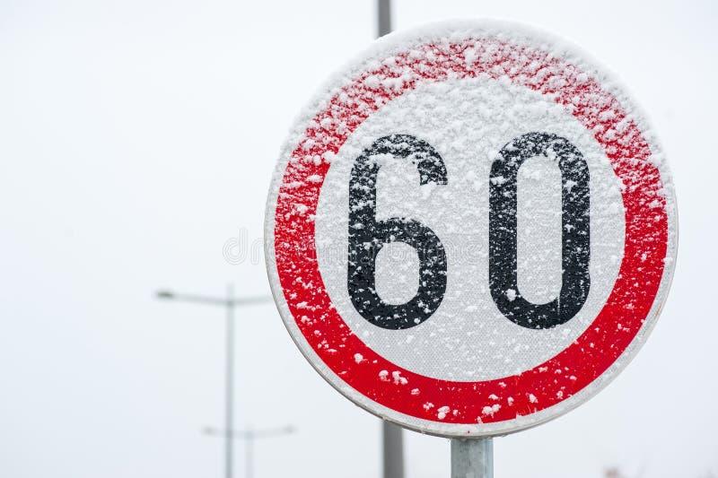 Tecken för trafikväghastighetsbegränsning 60 på gatan som täckas med för vintersäsong för insnöad fara halt slut upp royaltyfri fotografi