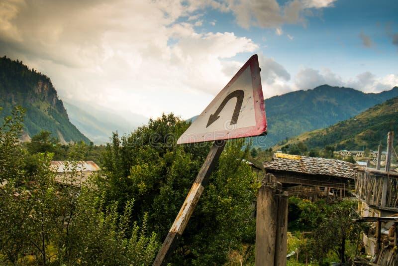Tecken för U-vändtrafik på den vita triangeln på vägen till det Rotang passerandet, himalaya royaltyfria bilder