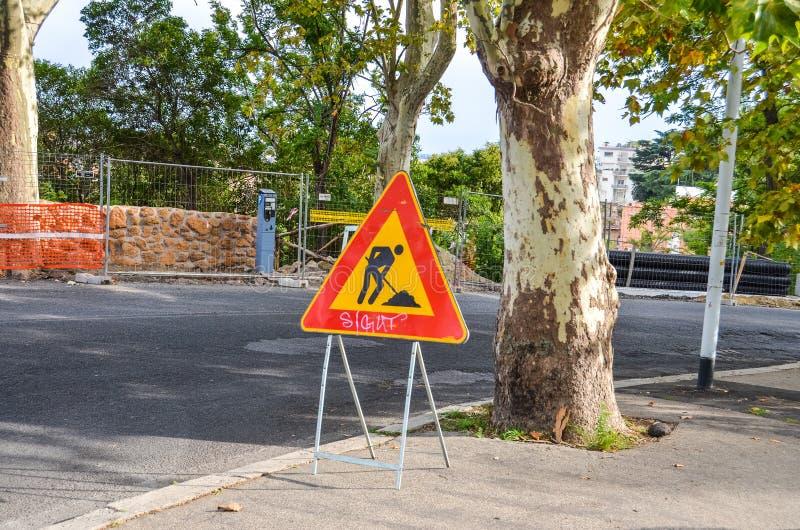 Tecken för vägarbeten på den soliga gatan arkivbild