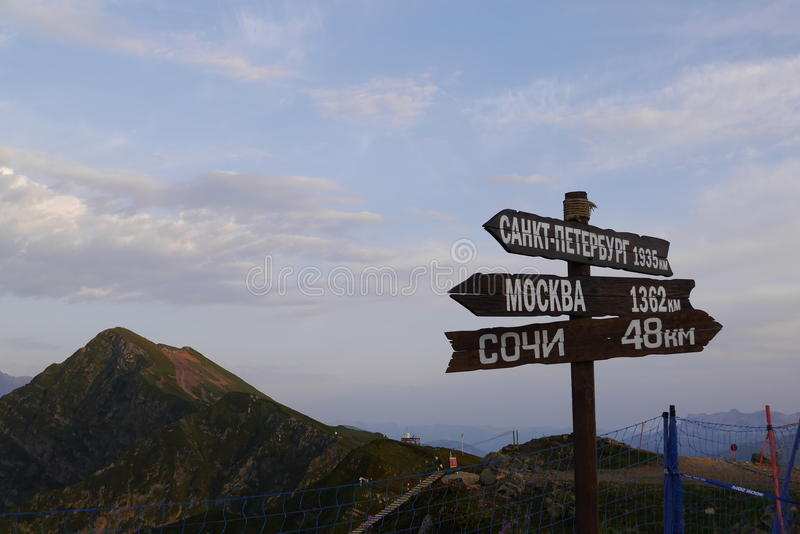 Tecken med riktningar och Kaukasus berg Rosa Khutor Sochi, Ryssland fotografering för bildbyråer