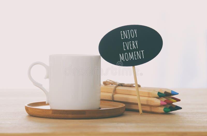 tecken med text: TYCK OM VARJE ÖGONBLICK bredvid koppen kaffe över trätabellen royaltyfri bild