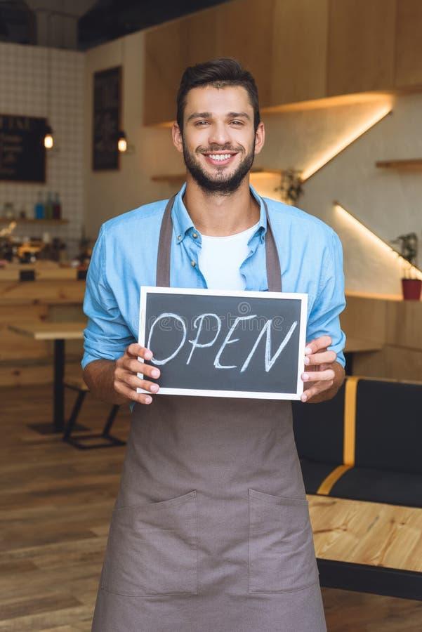 tecken och le för stiligt ungt innehav för små och medelstora företagägare öppet royaltyfri foto