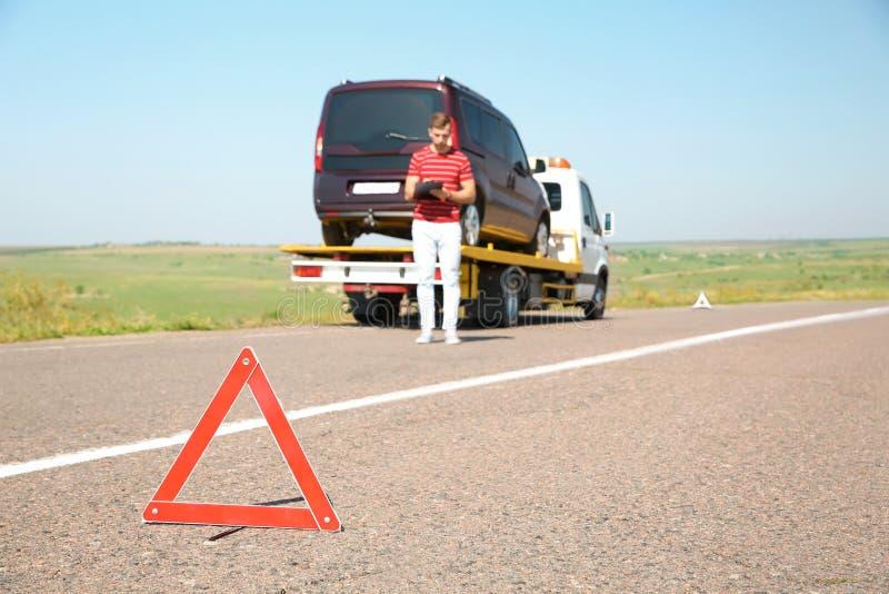 Tecken och man för nöd- stopp nära bärgningsbilen med den brutna bilen arkivfoto