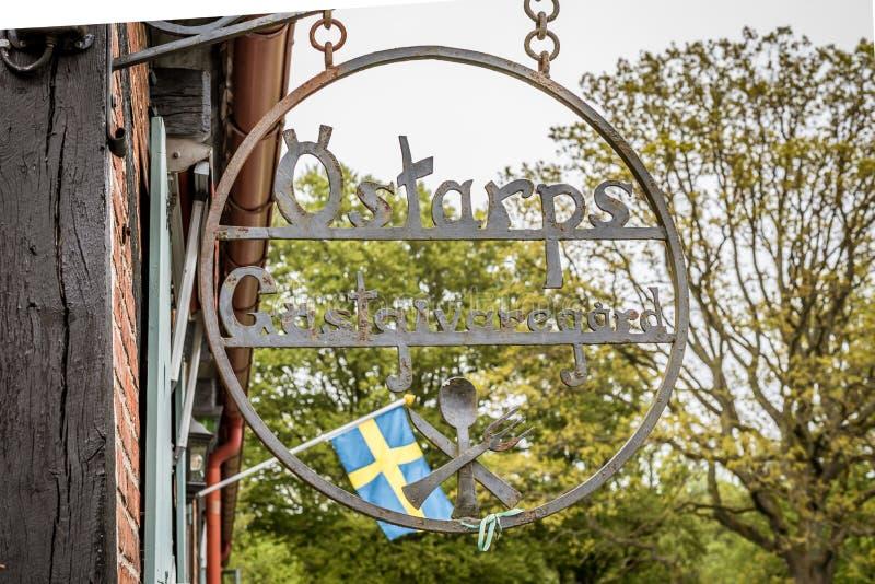 Tecken och svensk flagga utanför Kulturens Östarp, en äkta Skåne gästgivargård fotografering för bildbyråer