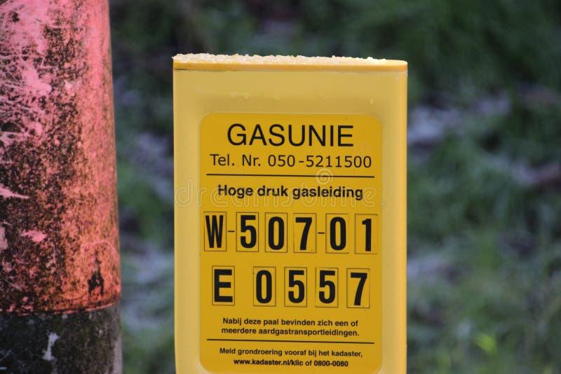 Tecken ovanför ett högtrycknaturgasrör med information om detalj att varna att röret är i jordningen arkivbild