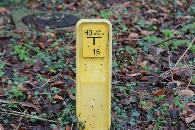 Tecken ovanför ett högtrycknaturgasrör med information om detalj att varna att röret är i jordningen royaltyfri foto
