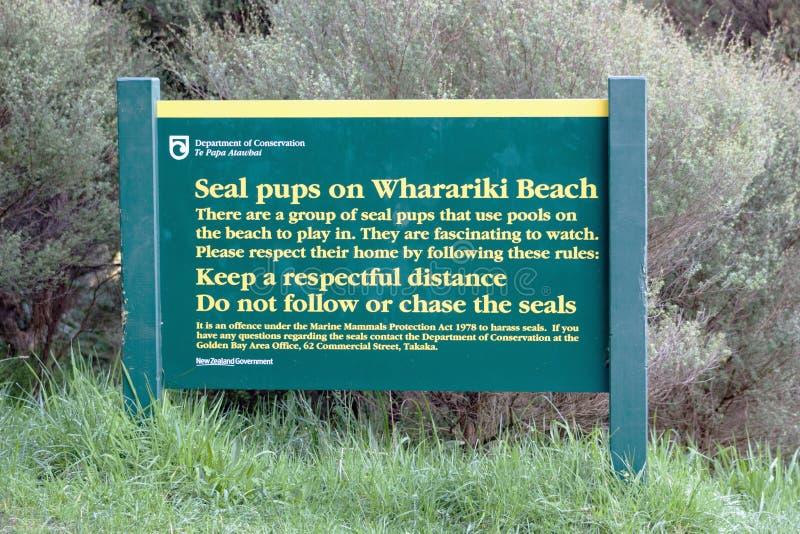 Tecken på den Wharariki stranden som råder om skyddsremsavalper i området fotografering för bildbyråer