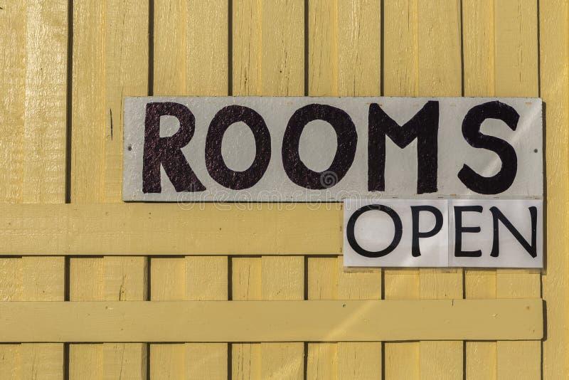 Tecken`-rum öppnar ` på gul trätexturerad bakgrundsindicatin royaltyfri bild