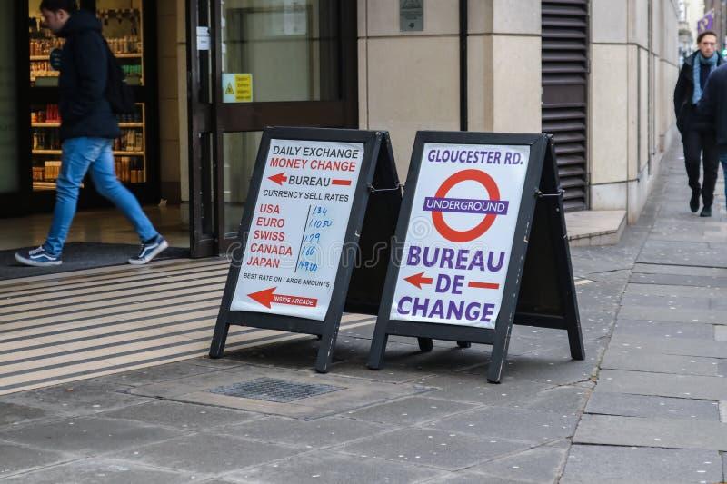 Tecken som står på trottoaren som inom pekar för pengarutbytet och listar olika valutor på Glouster Rd tunnelbanast royaltyfri bild