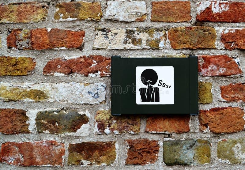 Tecken/symbol av förfrågan för tystnad/muta på tegelstenväggen i Bruges/Brugge, Belgien royaltyfri bild