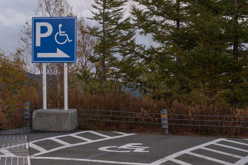 Teckenhandikappade personer, detalj av en signal i en parkeringsservice fotografering för bildbyråer