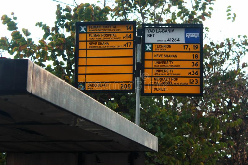 Teckenplatta med namn av lokala hållplatser och stadsbussruttar i Haifa, Israel royaltyfria foton