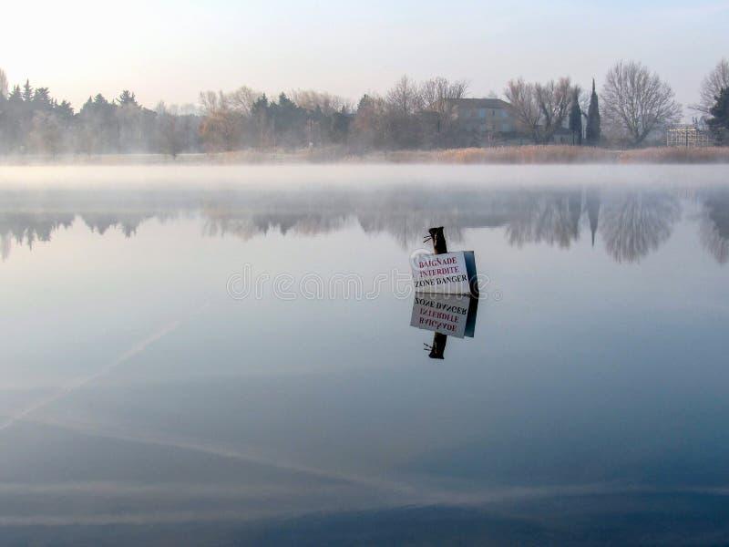 Teckenstolpen i den dimmiga morgonsjön reflekterad i kallt vatten, farlig områdessimning för varning förböd arkivbilder