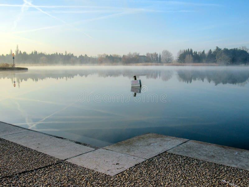 Teckenstolpen som reflekterar i kallt vatten som en spegel, farlig områdessimning för varning, förböd fotografering för bildbyråer