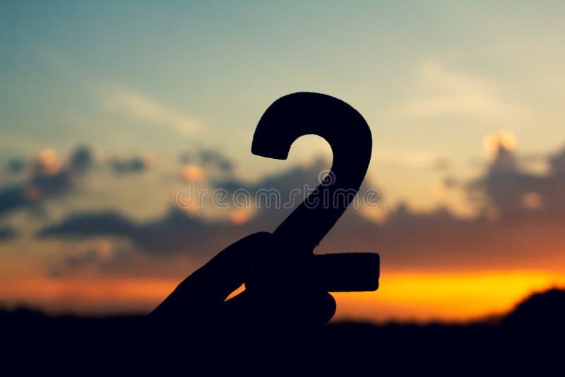 Teckensymbol för nummer två av trätext 2 på aftonnatursolnedgången, härligt moln royaltyfri bild