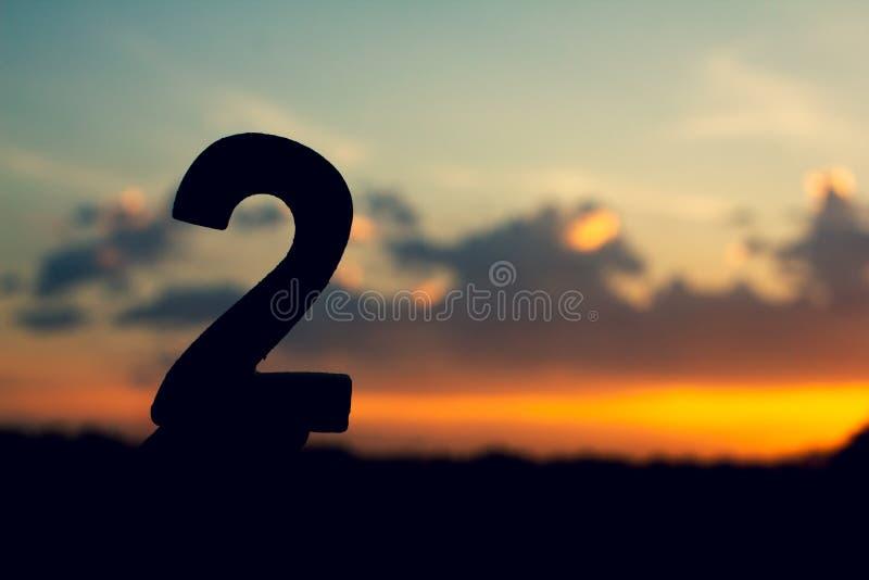 Teckensymbol för nummer två av trätext 2 på aftonnatursolnedgången, härligt moln royaltyfria bilder