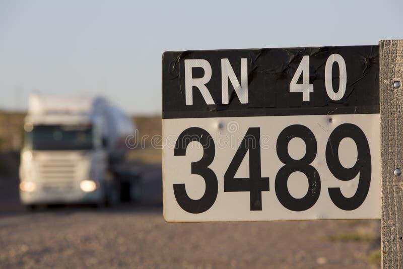 Teckenväg och lastbil för rutt 40 i nord av Argentina royaltyfri fotografi